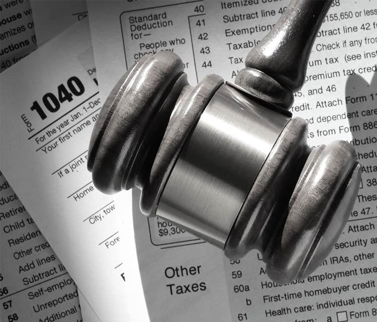 Tax paperwork with a hammer as used in court on top, image in close up